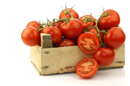 tomato soup: fresh tomatoes on the vine and a cut one in a wooden crate on a white background