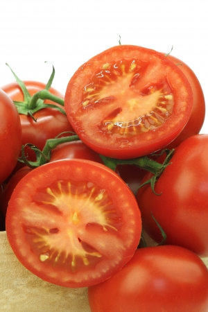 fresh tomatoes on the vine and a cut one in a wooden crate on a white background Stock Photo - 15085861