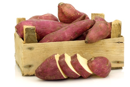 Bunch of sweet potatoes and a cut one in a wooden crate on a white background