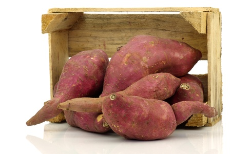 Bunch of sweet potatoes in a wooden crate on a white background