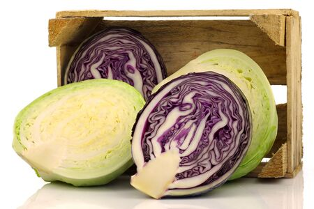 freshly cut red and white cabbage in a wooden crate on a white background  photo