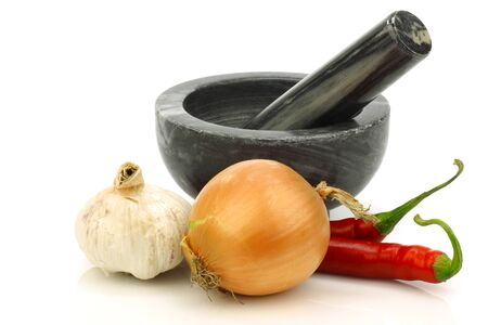 mortar and pestle and some fresh vegetables on a white background  Stock Photo - 15085845