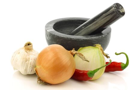 mortar and pestle and some fresh vegetables on a white background Stock Photo - 15085857