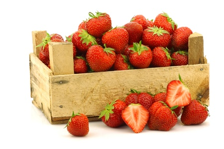 fresh strawberries and a cut one in a wooden box  photo