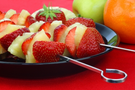 fresh strawberry halves and pieces of pineapple on a skewer on a black plate  photo