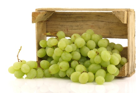fresh white grapes in a wooden crate on a white background  photo