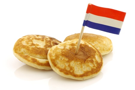 freshly baked traditional Dutch mini pancakes called  poffertjes  with a Dutch flag toothpick on a white background  photo