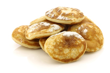 powdered sugar: freshly baked traditional Dutch mini pancakes called  poffertjes  with powdered sugar on a white background  Stock Photo