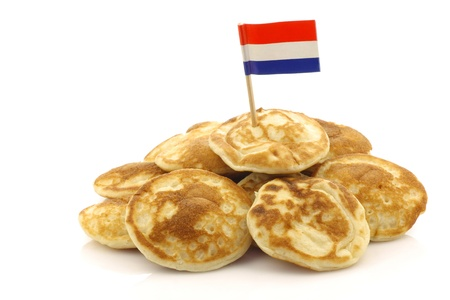 freshly baked traditional Dutch mini pancakes called  poffertjes  with a Dutch flag toothpick on a white background  Banque d'images