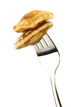 freshly baked traditional Dutch mini pancakes called  poffertjes  on a fork on a white background