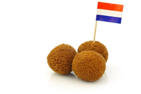 A real traditional Dutch snack called  bitterballen  with a Dutch flag toothpick on a white background  photo