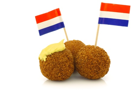 A real traditional Dutch snack called  bitterballen  with mustard and a Dutch flag toothpick on a white background