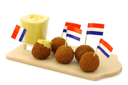 A real traditional Dutch snack called  bitterballen  with a Dutch flag toothpick on a wooden cutting board on a white background  Stock Photo