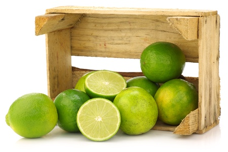 fresh lime fruit in a wooden crate on a white background  版權商用圖片