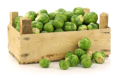 freshly harvested brussel sprouts in a wooden crate on a white background
