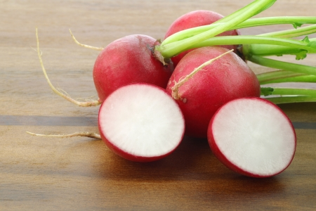 resh radishes and a cut one on a on a wooden cutting board Stock Photo - 15081585