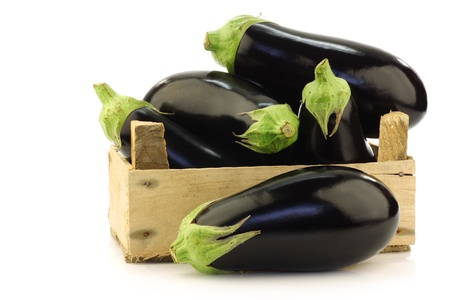 fresh aubergines in a wooden crate on a white background