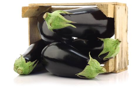 fresh aubergines in a wooden crate on a white background  photo