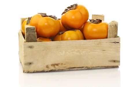persimmon: fruta fresca kaki en una caja de madera en un fondo blanco