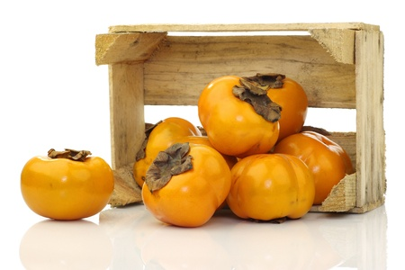 fresh kaki fruit in a wooden crate on a white background photo