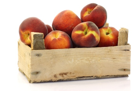 freshly harvested peaches in a wooden crate on a white background  Stock Photo