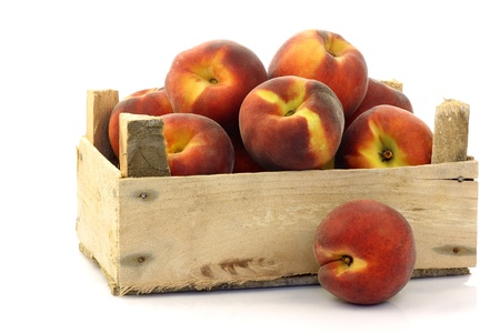 freshly harvested peaches in a wooden crate on a white background 版權商用圖片 - 15081531