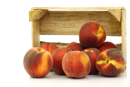 peaches: freshly harvested peaches in a wooden crate on a white background  Stock Photo