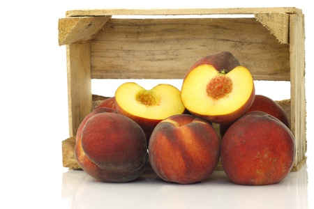 freshly harvested peaches and a cut one in a wooden crate on a white background  photo