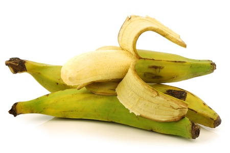 fresh still unripe plantain  baking  banana and a peeled one on a white background