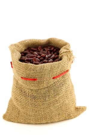 bean bag: red kidney beans in a burlap bag and an aluminum scoop on a white background