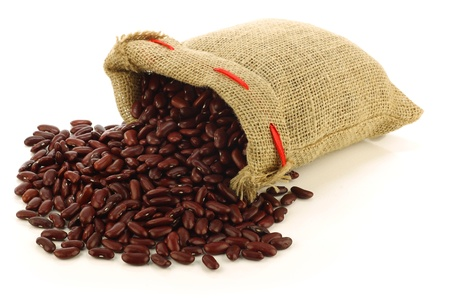 red kidney beans in a burlap bag and an aluminum scoop on a white background  Stock Photo - 15106525