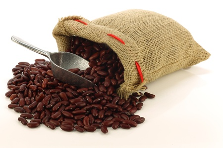 red kidney beans in a burlap bag and an aluminum scoop on a white background