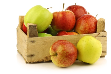 assorted fresh apples in a wooden crate on a white background  Фото со стока