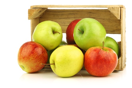 mixed fruit: assorted fresh apples in a wooden crate on a white background