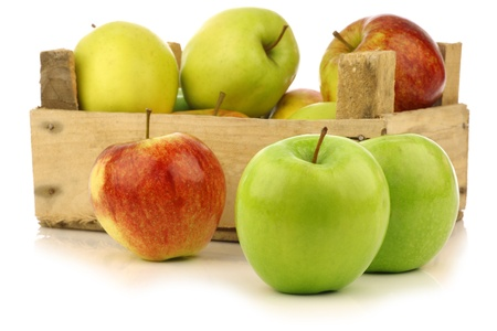 golden apple: assorted fresh apples in a wooden crate on a white background  Stock Photo