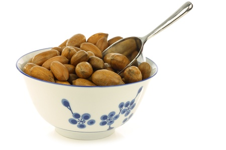 anti oxidants: tasty pecan nuts in a ceramic bowl with a metal scoop on a white background