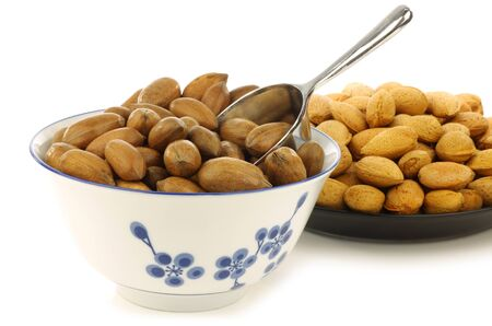tasty pecan nuts in a ceramic bowl and almonds on a black plate with a metal scoop on a white background  Stock Photo