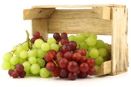 bunch of grapes: red and white grapes in a wooden box on a white background  Stock Photo