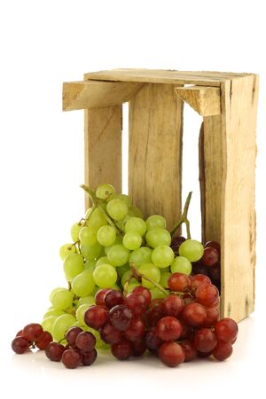 red and white grapes in a wooden box on a white background  photo