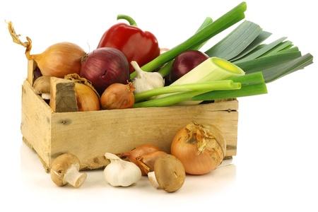 cebolas: legumes variados frescos em uma caixa de madeira em um fundo branco