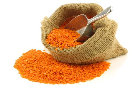 red lentils in a burlap bag with a metal scoop on a white background