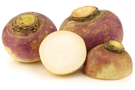 fresh turnips and a cut one on a white background