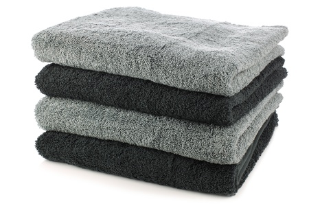 laundry pile: stacked black and grey bathroom towels on a white background  Stock Photo