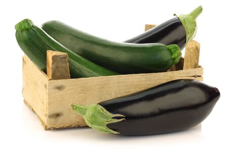 fresh zucchini s  Cucurbita pepo  and eggplant in a wooden box on a white background