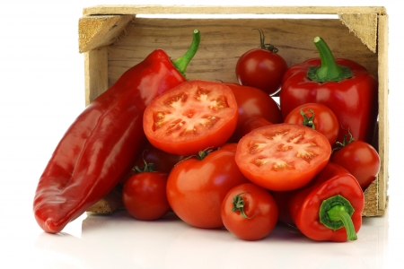 red sweet peppers, tomatoes and a cut one in a wooden crate on a white background  photo