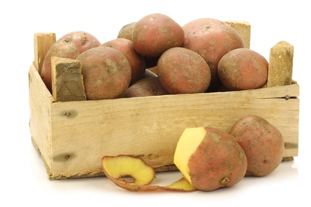 freshly harvested dutch potatoes called  Bildtstar  and a peeled one in a wooden crate on a white background  Stock Photo