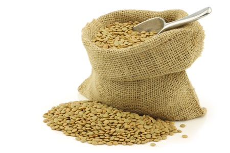 green dried lentils in a burlap bag with an aluminum scoop on a white background