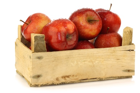 apple tree: Fresh and delicious red Ambrosia apples in a wooden crate on a white background
