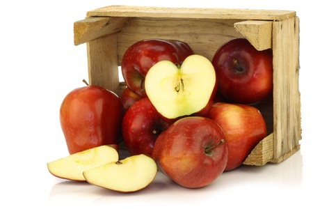 ambrosia: Fresh and delicious red Ambrosia apples and a cut one in a wooden crate on a white background  Stock Photo