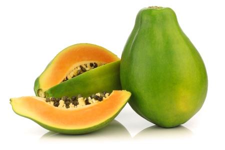 fresh papaya fruit and a cut one on a white background